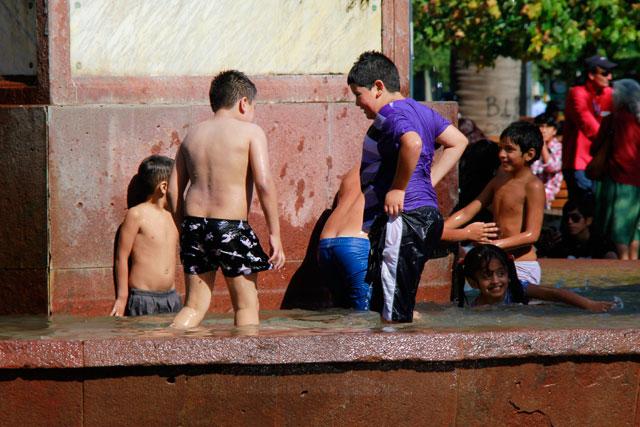 Crianças brincam na fonte, na Plaza de Armas