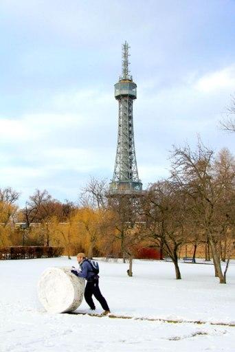 Jovem faz rolo de neve, em Petřín