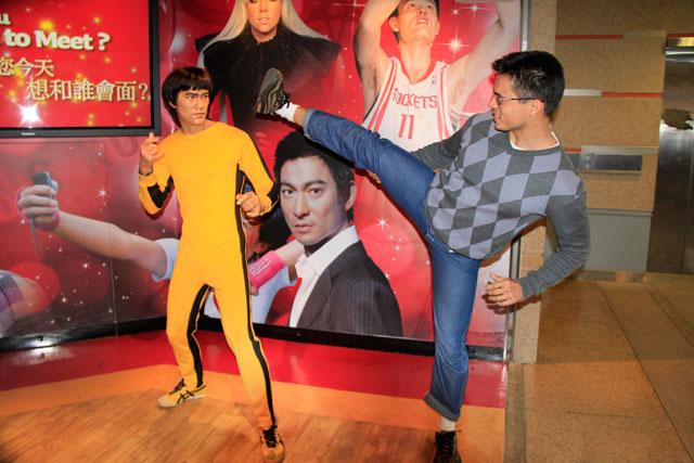Tião luta contra estátua de cera de Bruce Lee, próximo à entrada do Madame Tussauds