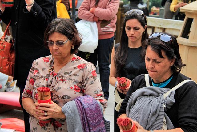Maria, Yáskara e minha mãe fazem pergunta enquanto chacoalham copo com palitos