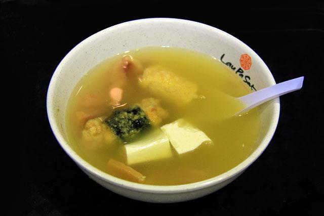Sopa com tofu, ovo, polvo, e carne de porco servida no Lau Pa Sat
