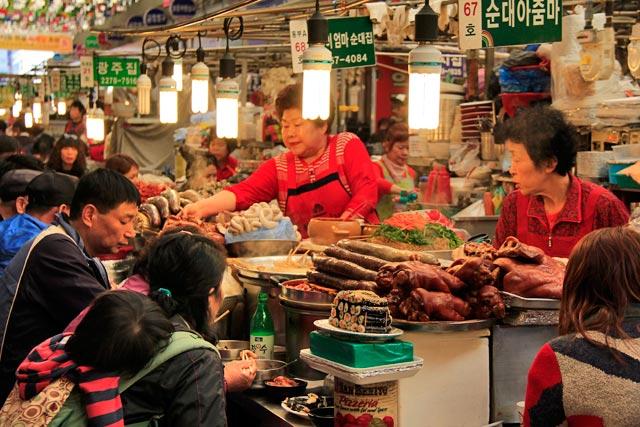 Ajummas servem refeições típicas no Mercado de Kwangjang