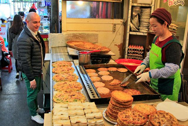 Aguardo o preparo do bindaetteok, no mercado de Kwangjang