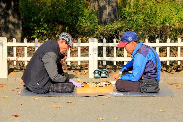 Senhores se divertem com o go, em praça ao lado do Santuário de Jongmyo