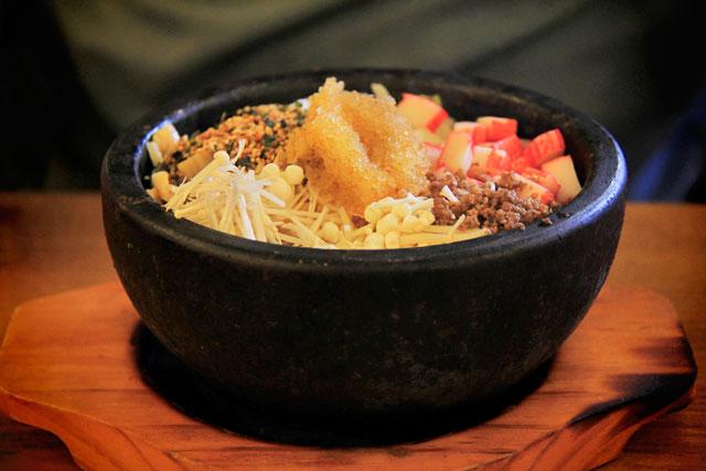 Arroz com kani, gergelim, ovas de peixe, broto de feijão, repolho, carne moída e cogumelo, no Yookssam Naengmyeon