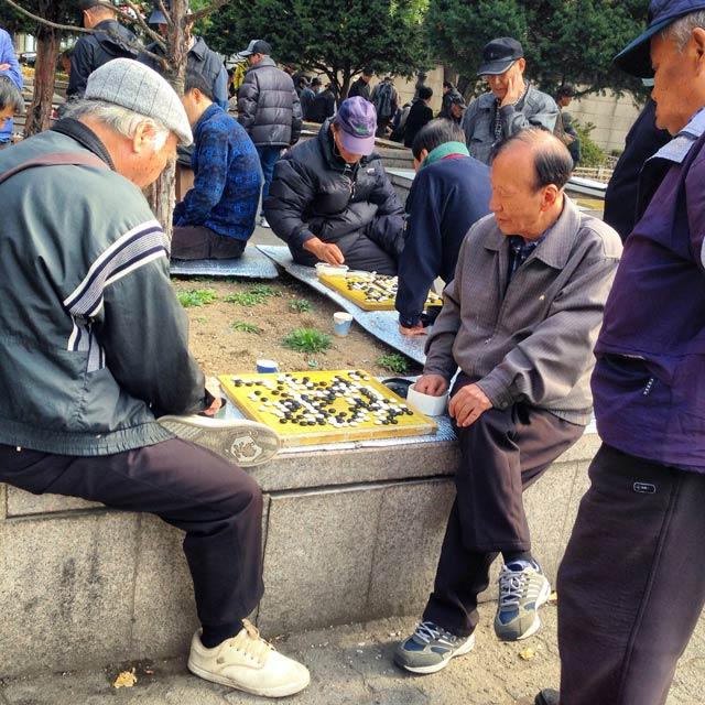 Senhores se divertem com o go, em praça ao lado do Santuário de Jongmyo (via Instagram)