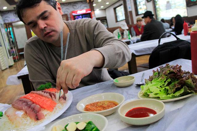 Élcio degusta sua bandeja de sashimi, em restaurante do Noryangjin