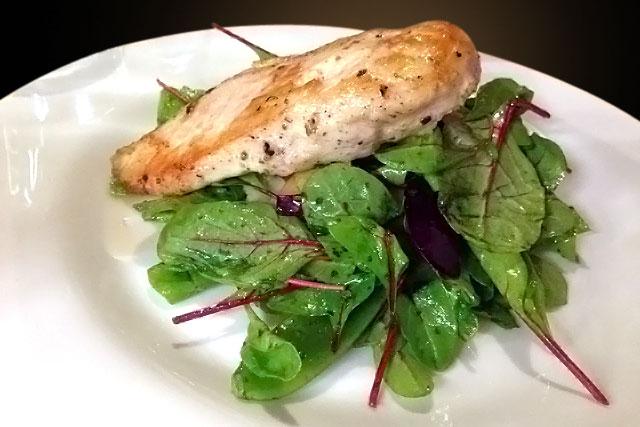 Peito de frango com ameixas e folhas de beterraba servido no Etno Baras